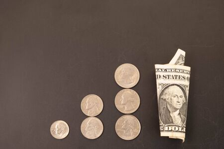Money, US Dollars bank notes, penny, nickel, dime, quarter on black background. Finance and economy concept.