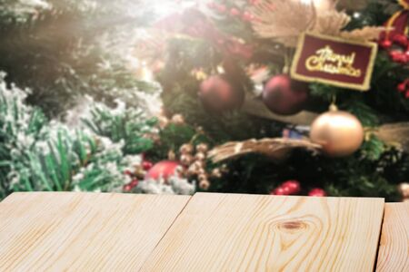 Perspective empty wooden table and christmas tree blur decoration background, for product display montage or design layout. Imagens