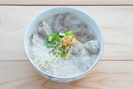 Congee with minced pork, braised pork filling, boiled pork liver, fried garlics minced pork in white bowl. Asian breakfast.