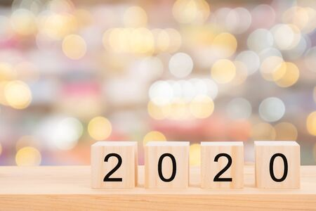 Happy new year 2020 text on wooden cubes on wooden pine table and blur light bokeh background. Banner with copy space for text. Imagens
