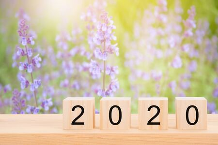 Happy new year 2020 text on wooden cubes on wooden pine table and blur purple flower background. Banner with copy space for text.