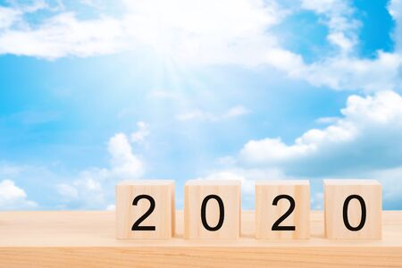 Happy new year 2020 text on wooden cubes on wooden pine table and blur blue sky background. Banner with copy space for text.