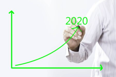 2020Text With Businessman Hand Point On Virtual Graph Green line.