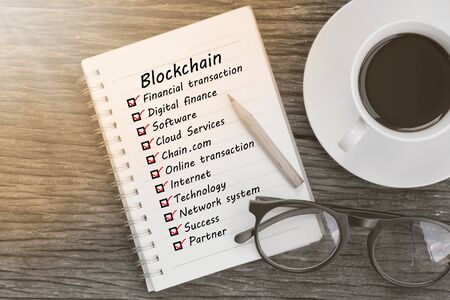Blockchain word and check list marks in notebook with glasses, pencil and coffee cup on wooden table. Project management concept.