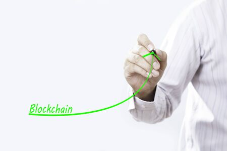 Businessman hand writing growth graph for blockchain.