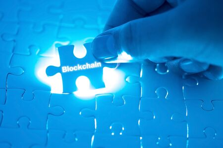 Blockchain word on jigsaw puzzle. Businessman hands holding white puzzle business concept. Business concept. Imagens