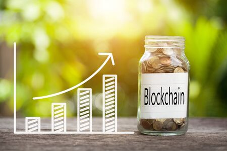 Blockchain Word With Coin In Glass Jar and graph up. Business Concept Imagens