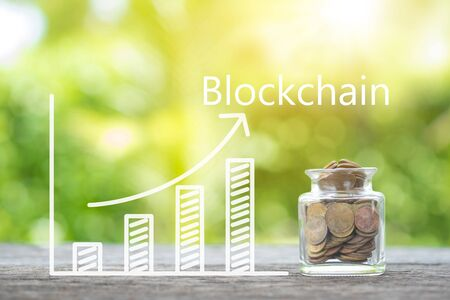 Blockchain word on savings coins and growing graph on wooden. Business concept. Imagens