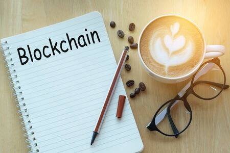 Concept blockchain message on notebook with glasses, pencil and coffee cup on wooden table.  Sunlight in the morning. Imagens