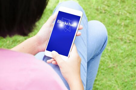 Top view of woman using her mobile phone with blockchain word. Business concept. Imagens