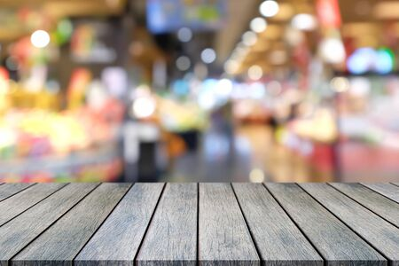 La table en bois vide de perspective sur le dessus sur fond flou, peut être utilisée comme maquette pour l'affichage des produits de montage ou la mise en page de conception.