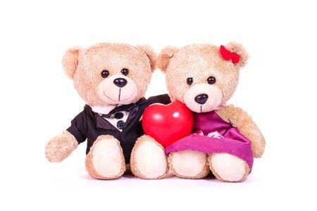Reizender Teddybär in der Hochzeitskleidbräutigambraut und im roten Herzen sitzen auf weißem Hintergrund. Konzepthochzeit der Liebe und des Valentinsgrußes.