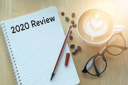 2020 review message on notebook with glasses, pencil and coffee cup on wooden table. Stock Photo