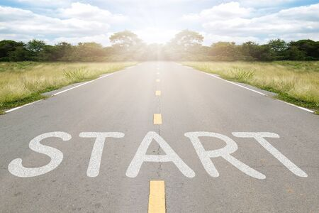 Start word writen on asphalt road with natural background. Zdjęcie Seryjne