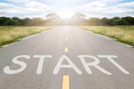 Start word writen on asphalt road with natural background. Imagens