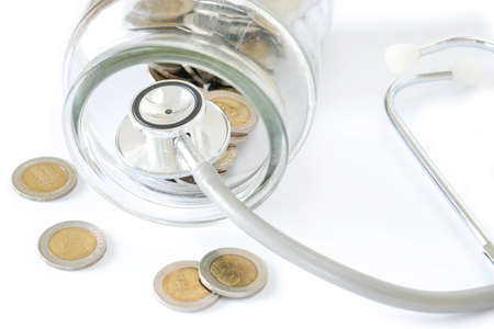 Stethoscope on bottle and coin on white background. Concept for finance health check or cost of business, financial analysis, audit or accounting.