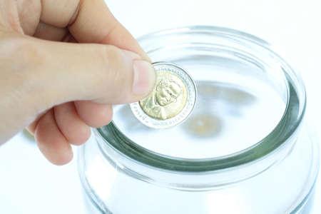 Close up women hands put coin in jar. Saving money growing business concept.