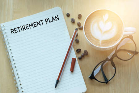 Retirement plan word on notebook with glasses, pencil and coffee cup on wooden table. Retirement plan concept. Фото со стока