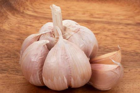 Garlic in wooden tray on wihte background. Close up garlic. Reklamní fotografie