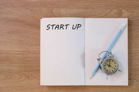 Start up concept on notebook with pencil and clock on wooden table. Business concept.