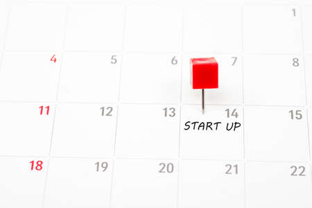 Start up written on a calendar with a red push pin to remind you and important appointment.