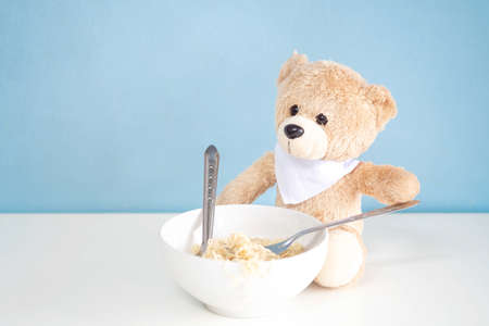 Teddy Bear sitting on a white table and eating noodle with blue background.