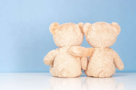 Two teddy Bear sitting on a white table and blue background. Imagens
