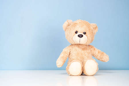 Teddy Bear sitting on a white table and blue background. Imagens