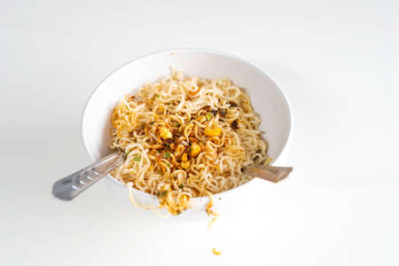 Instant noodles spicy ready to eat in the bowl with fork and spoon on white table wooden.