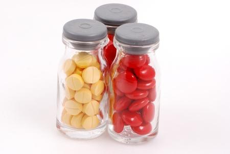 Pills in Glass Bottles on White Background
