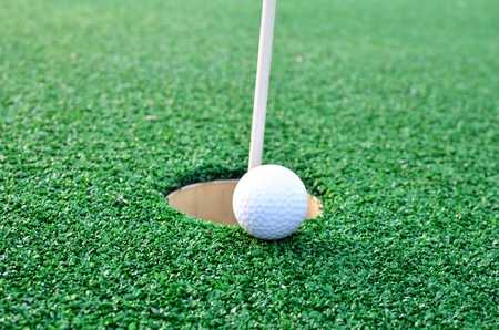 Golf ball sits at the lip of the hole on the putting green Stock Photo - 21896622