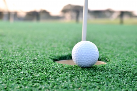 Golf ball sits at the lip of the hole on the putting green photo