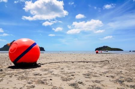 Orange buoy in the sand Stock Photo - 24055250