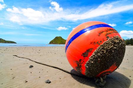 Orange buoy in the sand Stock Photo - 24055252
