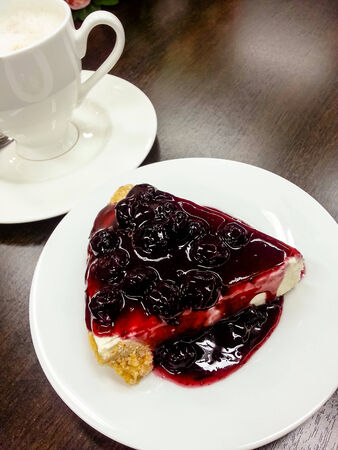 Cake blueberry with coffee cup in background