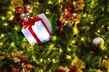 Decorating Christmas gift box on tree bright background