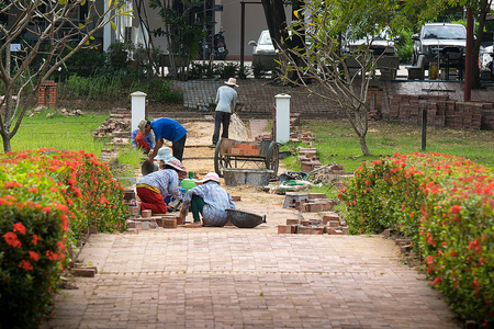 AYOTHAYA, THAILAND -Nov 11,2017: They construction. Repairing sidewalk. Worker laying stone paving slab. Laying colored tiles in city park (garden)