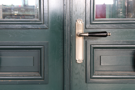 The Modern wooden door with metal door handle over the white wall. -Image