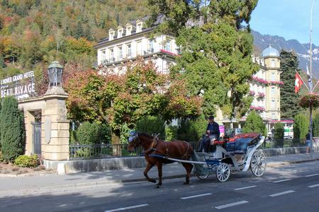 Interlaken, Switzerland - Oct 18 2018: Horse carriage waiting for passengers at Interlaken is a popular resort town lying between beautiful lakes in Interlaken, Switzerland