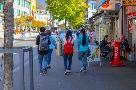Interlaken, Switzerland - Oct 18 2018: Tourists are walking to the Beautiful view of alpine Eiger village with hotels, restaurants, shops. Interlaken is a popular resort town lying between beautiful lakes in Interlaken, Switzerland Redakční