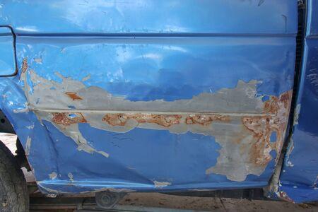 Close-up of old blue car paint broken, crack color of the automobile. Car paint cracks Фото со стока