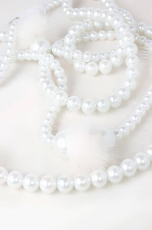 Pearl necklace over white background, high key shot