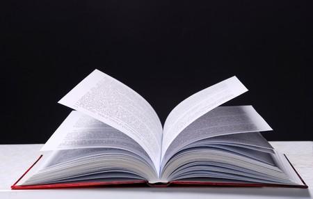 encyclopedias: Open book on dark background Stock Photo