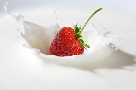 Delicious strawberry splashing into milk Stock Photo
