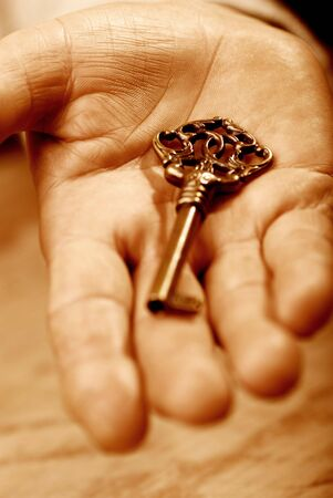 Hand with key, sepia tones photo