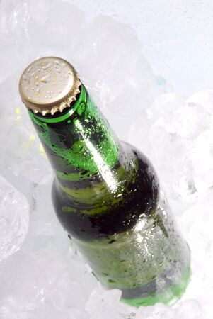 Green bottle of beer on ice  photo