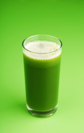 Green vegetable smoothie on green background photo