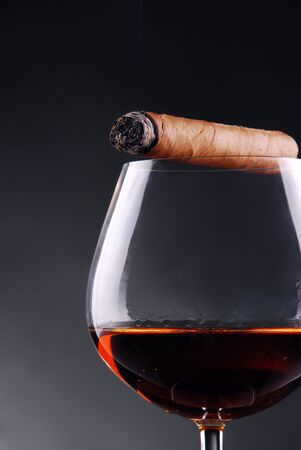 Glass of cognac with a cigar photo