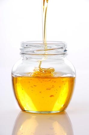 Pot met honing op witte achtergrond  Stockfoto