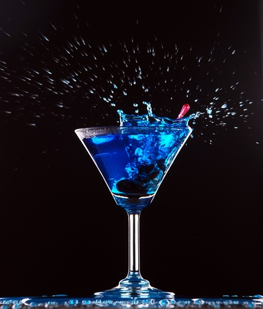 blue cocktail splashing on dark background photo
